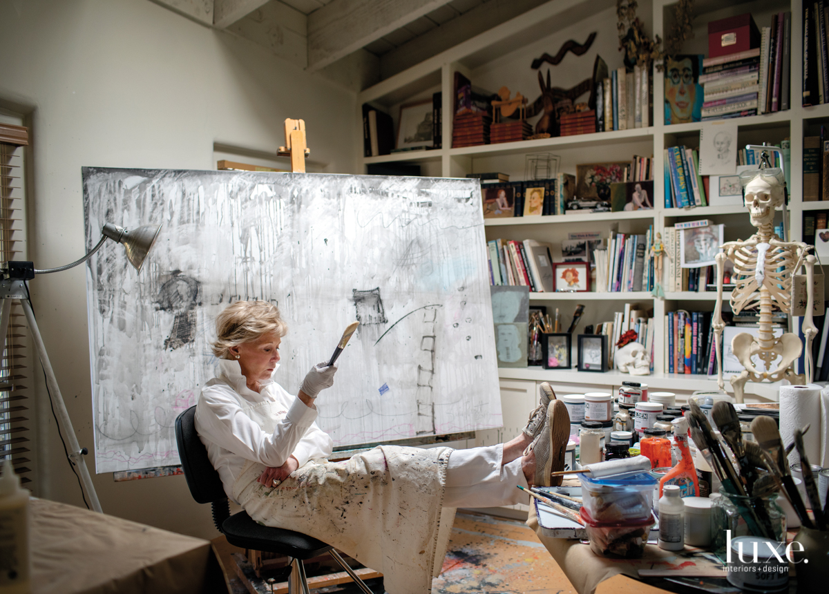 Pratt sits before a canvas in progress in her book- and art-filled studio.
