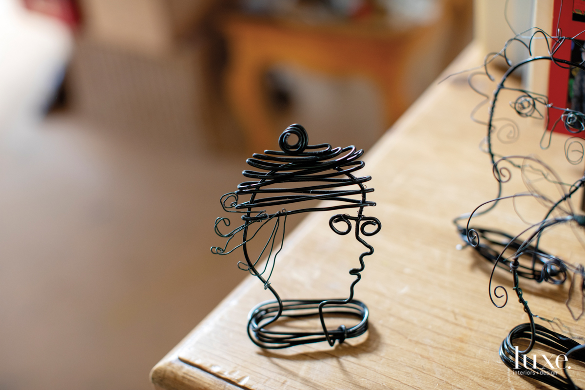 A wire sculpture head by the artist is one of a series.