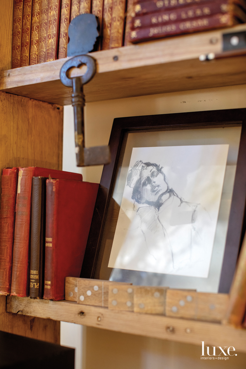 A pencil drawing rests on a shelf amid books and dominoes.