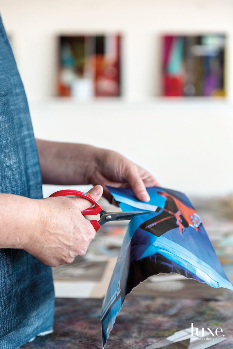 The artist uses scissors to excise images from magazines.