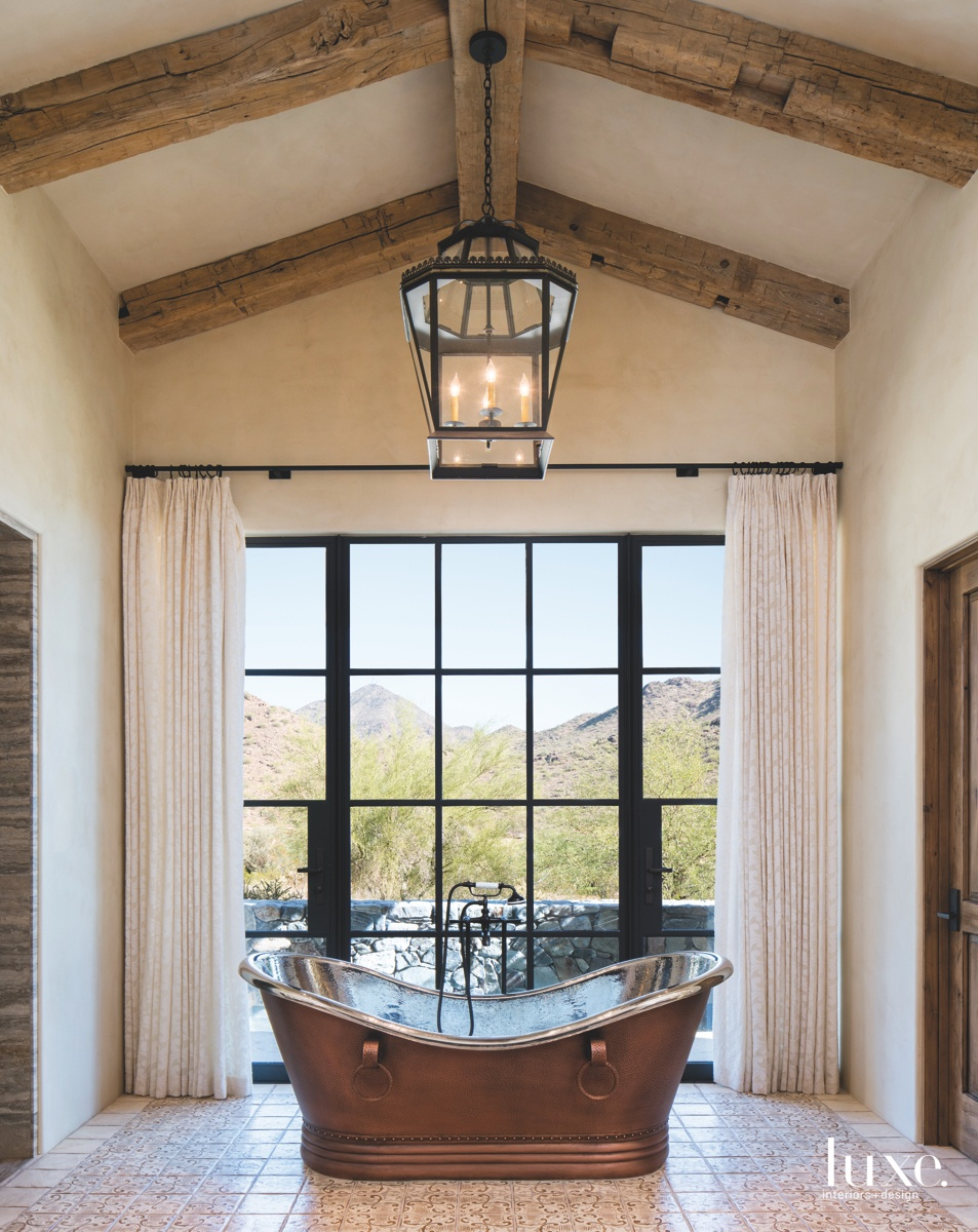 mediterranean bathroom freestanding iron-and-glass tub...