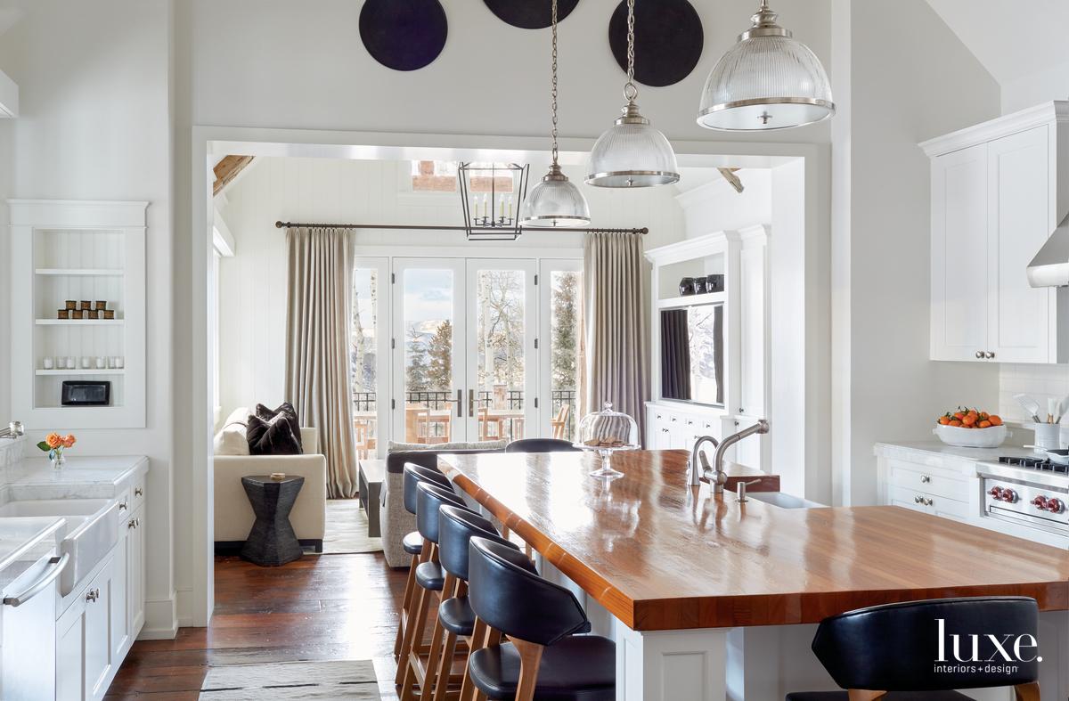 transitional white kitchen black stools...