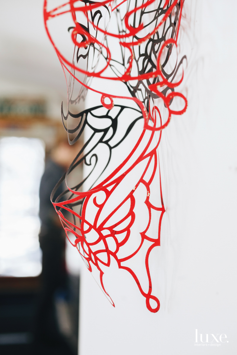 A piece of cut paper dangles in Robert Brinker's studio, before it is applied to canvas.