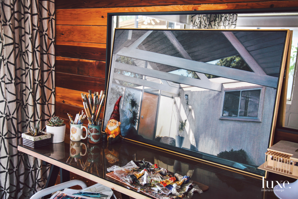 Danny Heller's desktop includes the tools of his craft along with a finished painting.