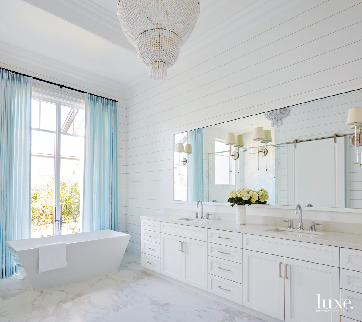 transitional white bathroom white cabinetry...