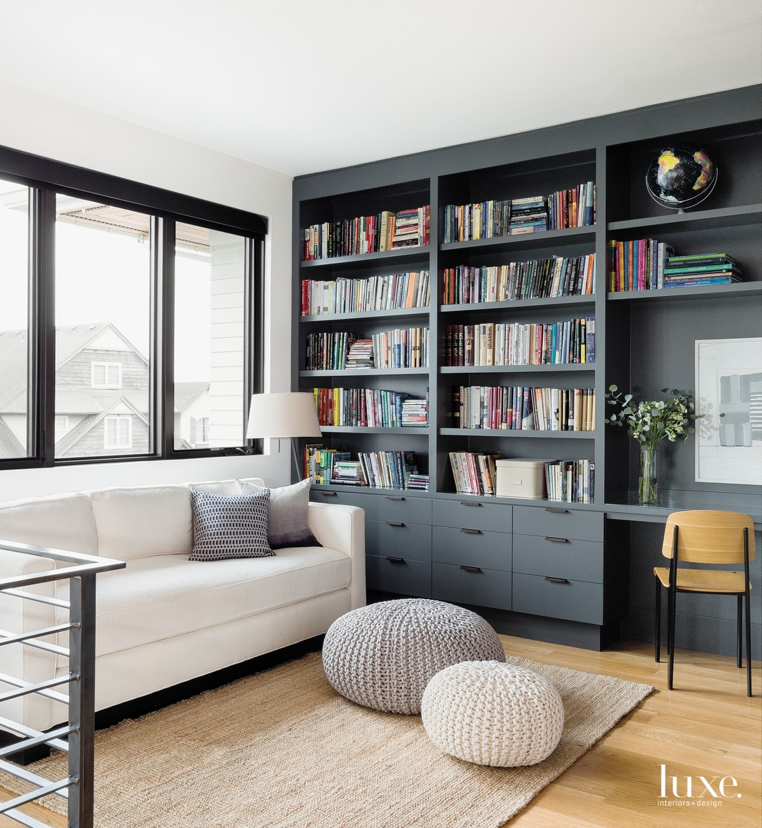 contemporary library loft black shelving white sofa poufs