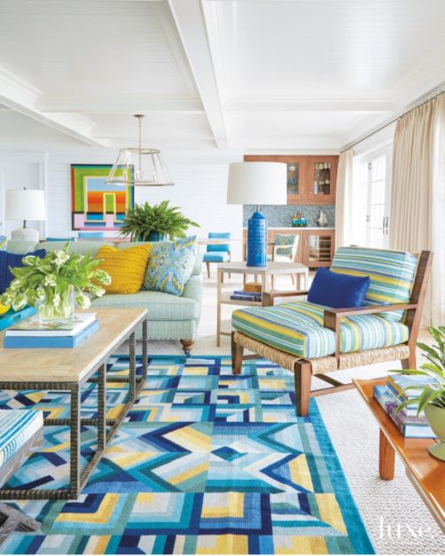 The living room's sisal rug from Stark is topped with a kaleidoscopic one from Vermilion Rugs; a Formations table with an iron base, from Holly Hunt, grounds the setting.