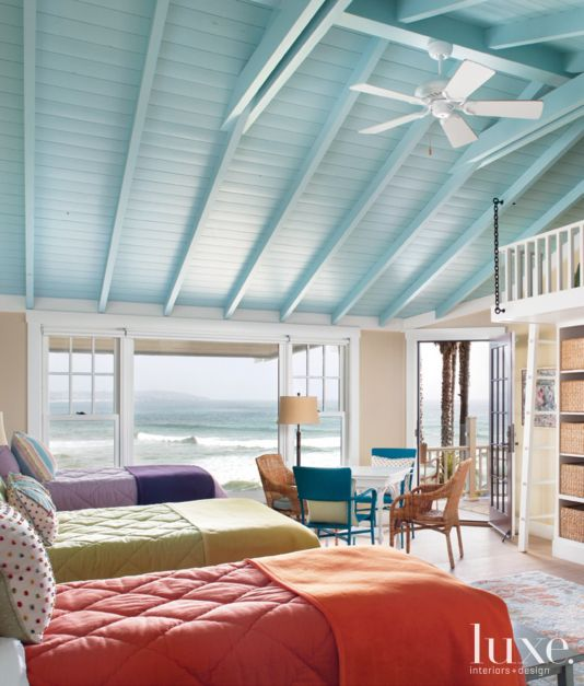 The second-story rooms, including the bunkroom, have European oak floors from DuChateau Floors. A light blue ceiling lends a relaxed feel to the room, which can sleep seven, thanks to a custom upper bunk bed designed by Sherwood. The colorful bedding is from Calico.