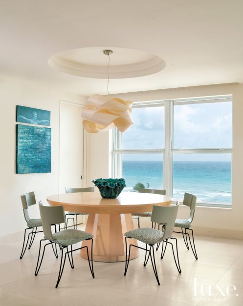 A ceiling recess adds depth to the dining area and delineates it from the kitchen, giving way to a Jolo Enterprises pendant, a maple dining table from Eric Brand in Burlingame, California, and Anziano chairs from Donghia wearing Cowtan & Tout fabric. Windows were replaced with ones from Innovative Window Concepts