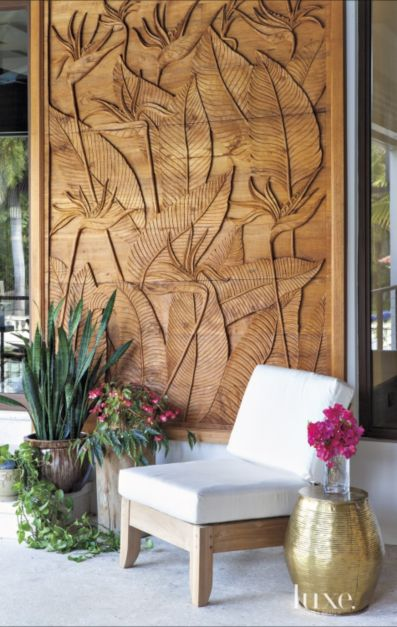 To conceal a water heater on the main-level terrace, the couple commissioned a handcrafted teak wall panel from Nongnit's Treasures in Thailand that depicts the husband's grandmother's favorite flower: the bird-of-paradise. The chair, from Holly Hunt, faces the pool on the deck below.