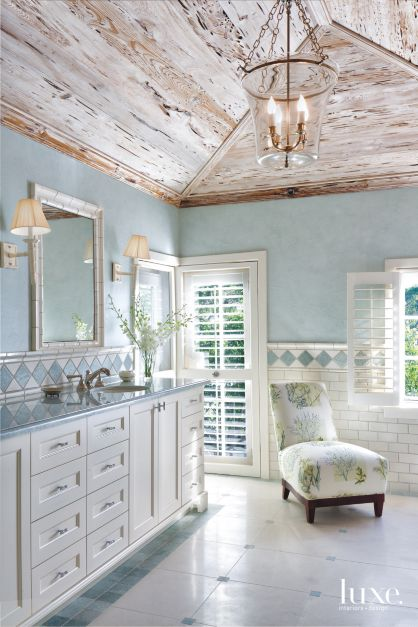 Builder Tim Givens opened up the ceilings in this Palm Beach master bathroom, giving them their arresting cathedral shape and cladding them in limed pecky cypress. It's a beautiful treatment that adds character and gives visual lightness to the space, which is further complemented by shellstone floors, creamy subway tile wainscoting and a pale blue-and-white palette chosen by designer Allison Paladino.