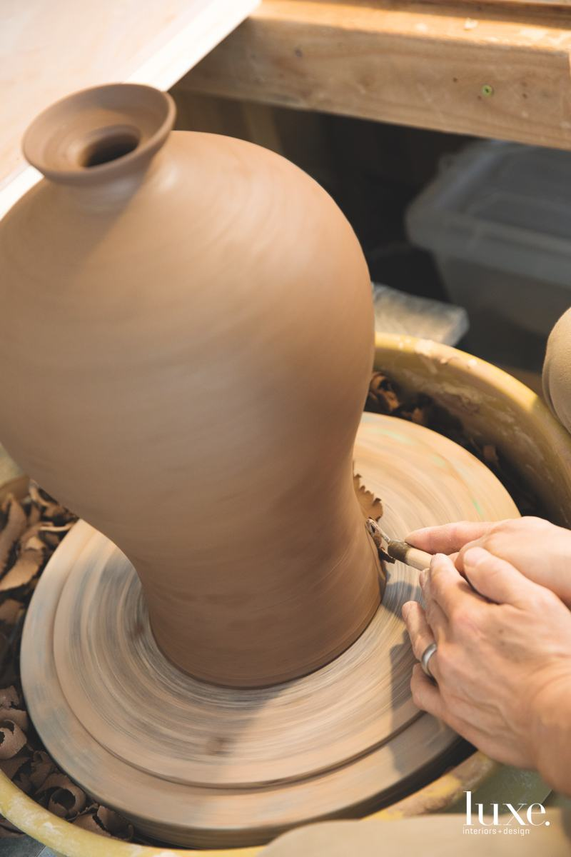 On the potter's wheel, a stoneware vessel takes shape.
