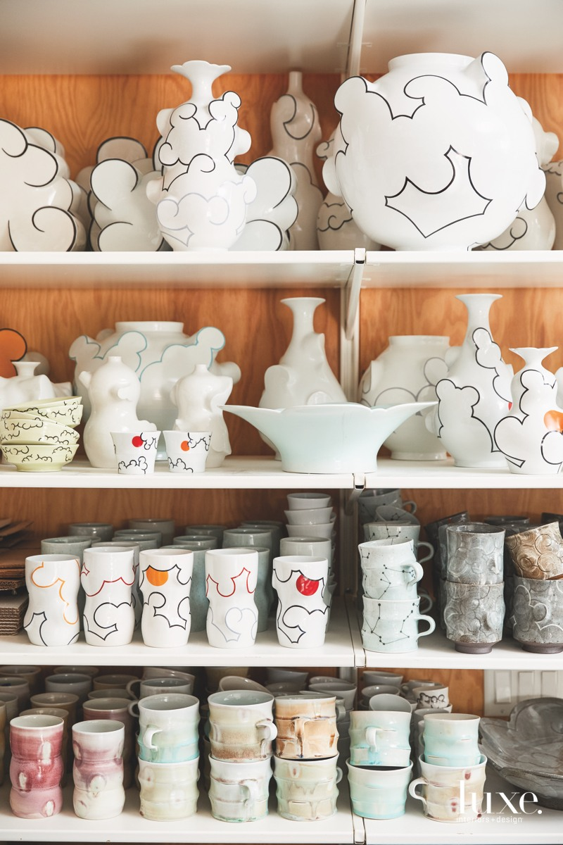 "A range of recent pieces fill the top shelf of a display of finished work; the middle shelf holds China-painted tumblers and Chung's new line of ""constellation"" cups, while the bottom displays soda-fired cups."