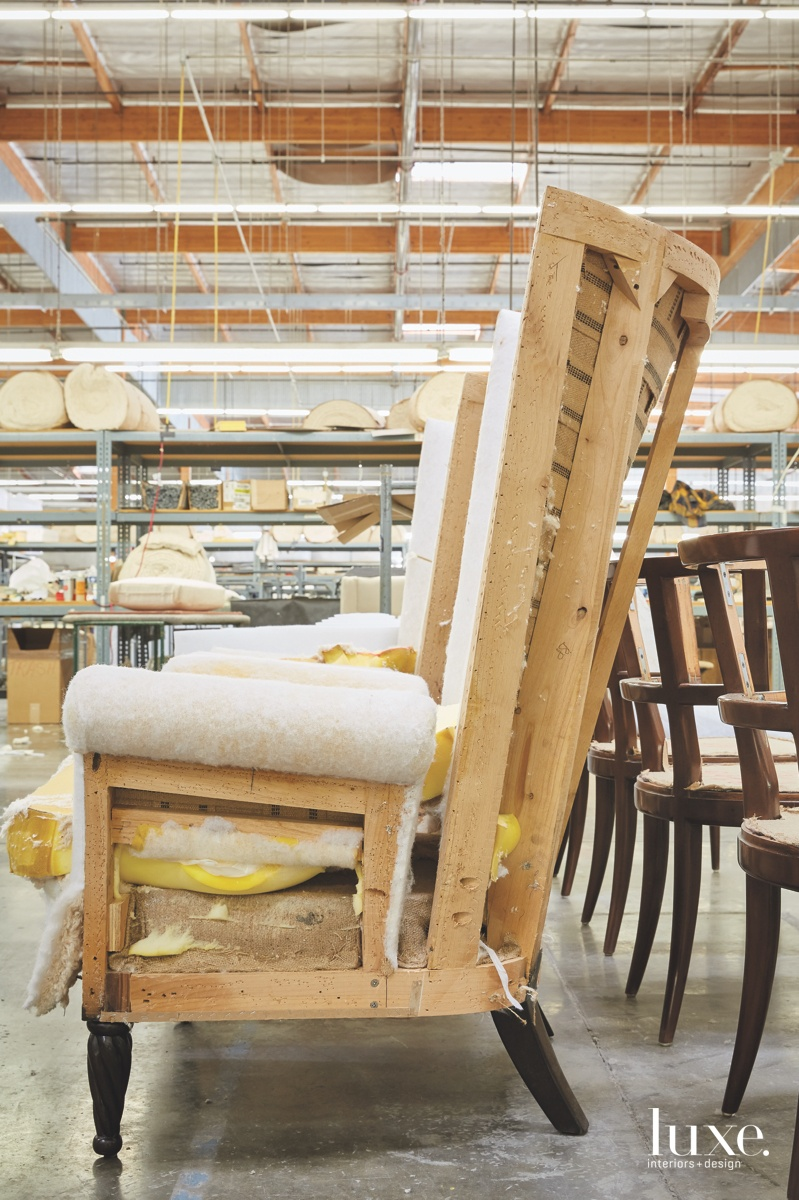 Showing off its great bones, a highback chair awaits upholstery on the factory floor.