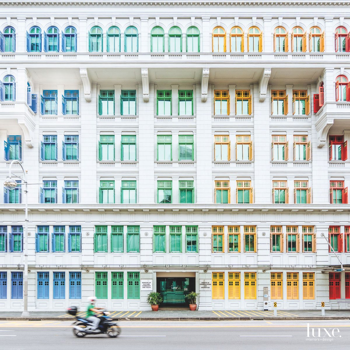 A virtual rainbow colors the window trim and shutters on the facade of a historic Singapore building in this photo by Marc Nouss.