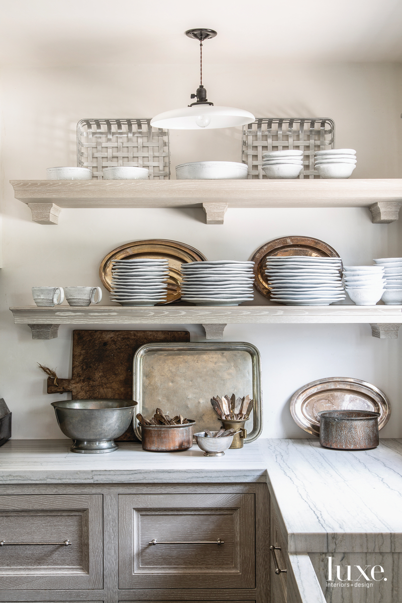 A collection of tabletop pieces lines the kitchen's open shelving. Gambrel sourced the vintage lighting found throughout the space.