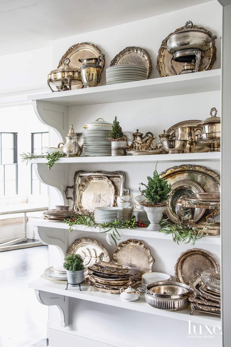 A few fresh touches accent the rows of statement silverware displayed in the kitchen including mini conifer trees, eucalyptus, chinaberries and red hypericum berries.