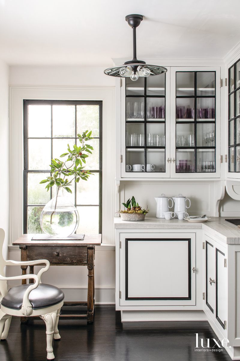 In the servery, a sculptural magnolia branch from a tree on the estate creates a dreamy scene. Positioned on the white quartzite countertops are planted amaryllis bulbs. The pendant light is by Rejuvenation.