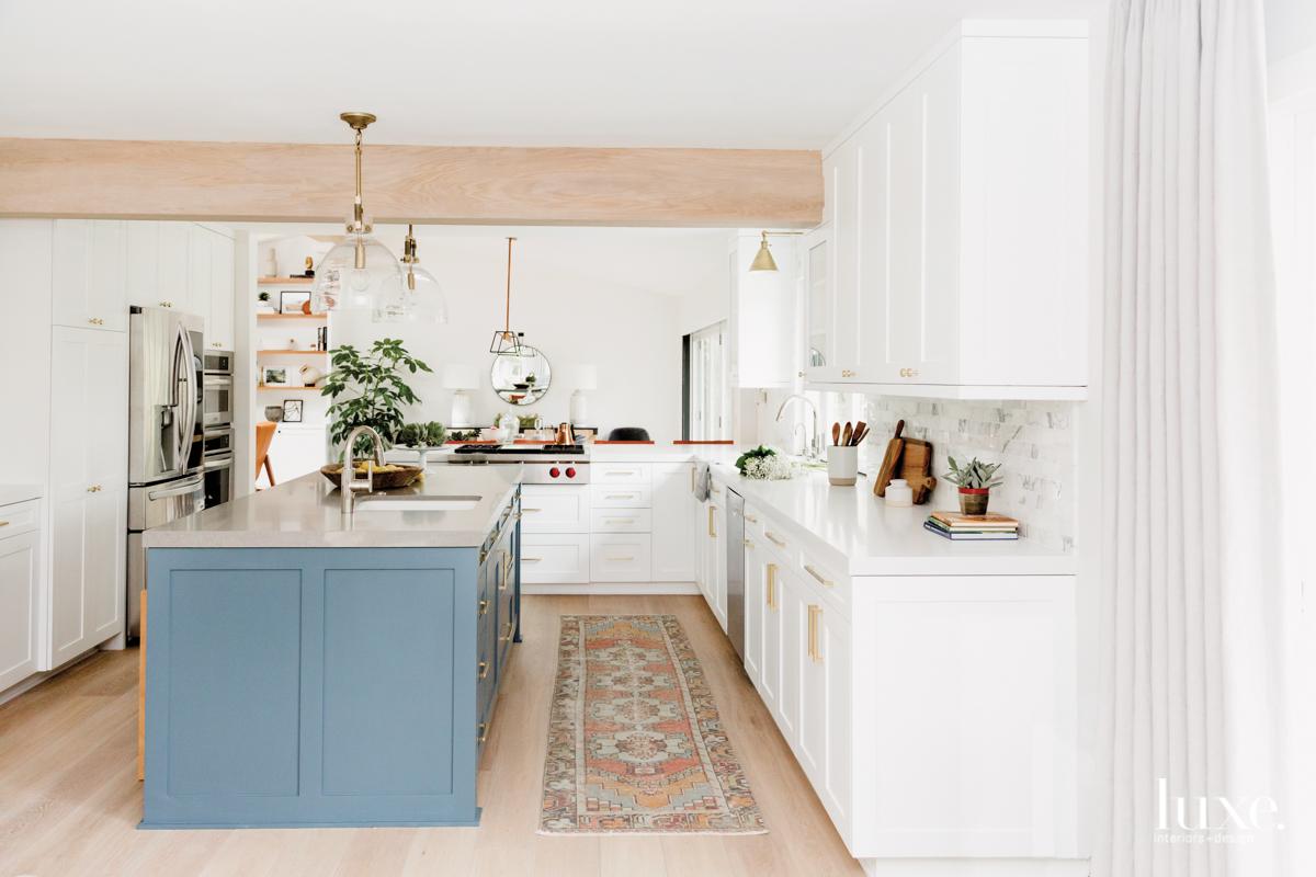 white kitchen blue island in...