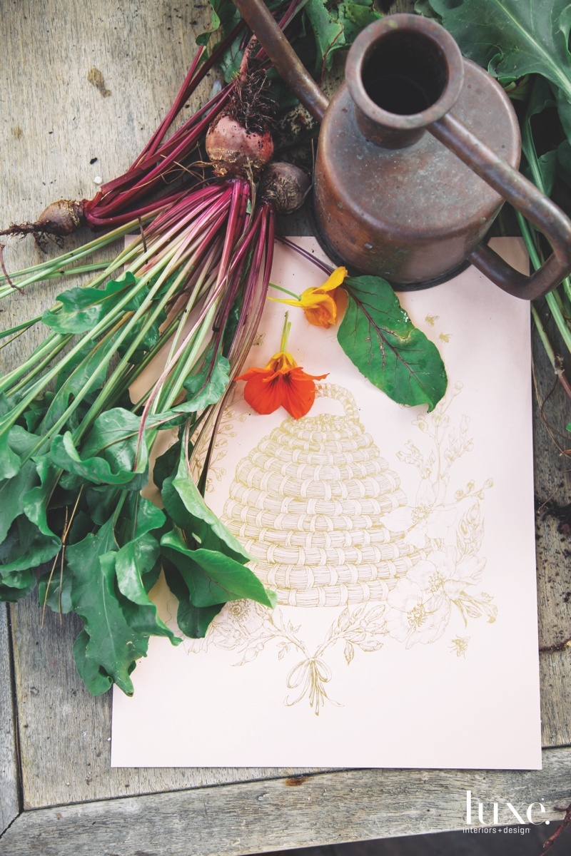 Beneath a bunch of fresh beets is a print of a bee skep, one of the botanical artworks that their design practice is known for.