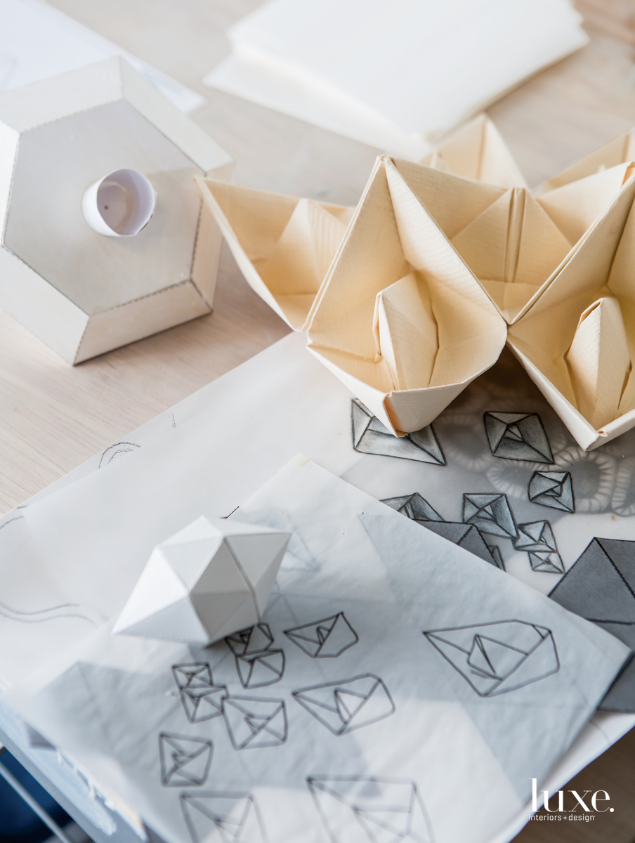 She made line drawings to plan an installation of 1,000 origami boats she folded over several months.