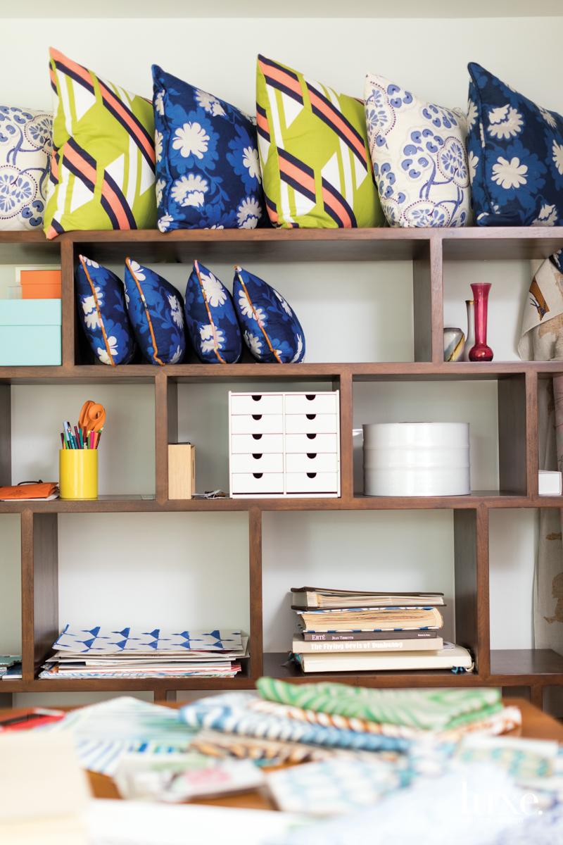 A bookshelf in textile designer Charlotte Osterman's studio showcases pillows covered in her Flower Child, Palampore Vine and Ribbon designs as well as inspirational items including photo albums from her travels and sketch books.
