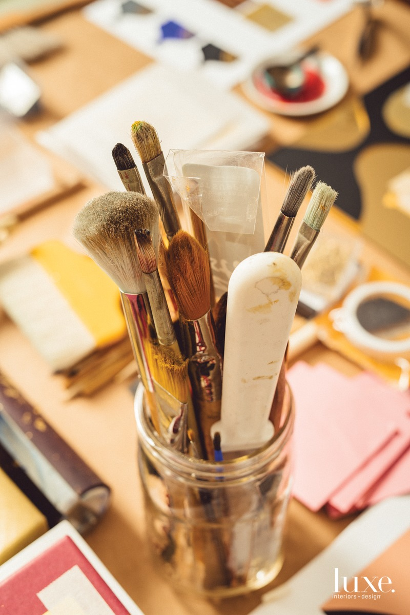 Hunt's work table holds her tools, including brushes and gold leaf.