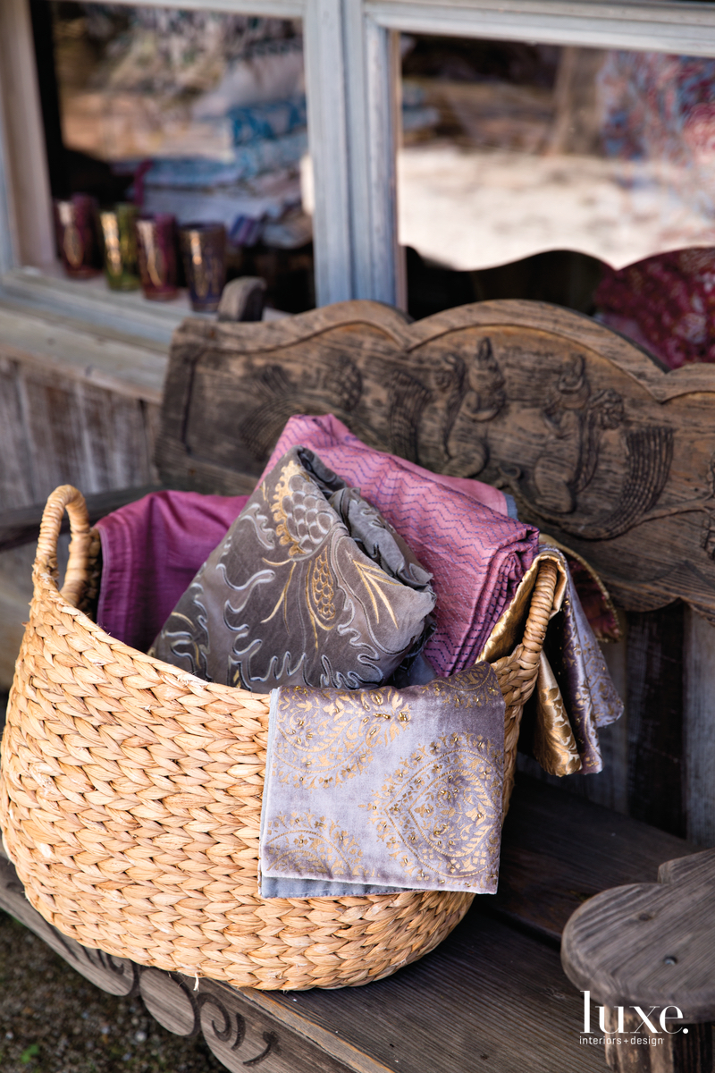 Purple hues are reflected in the fabrics seen in a woven basket.