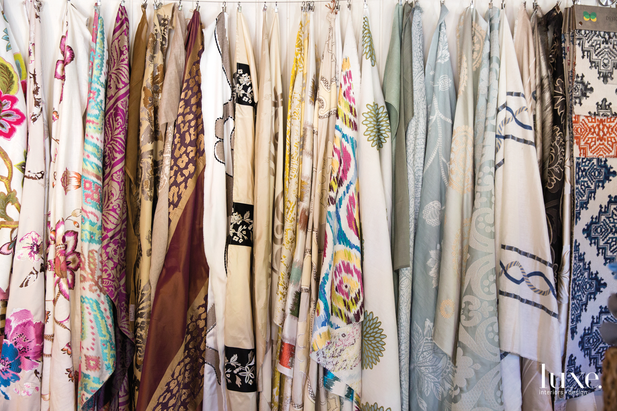 The designer started by importing and then embellishing pashminas, but today she oversees the creation of fabrics, some of which are displayed on the walls of her studio.
