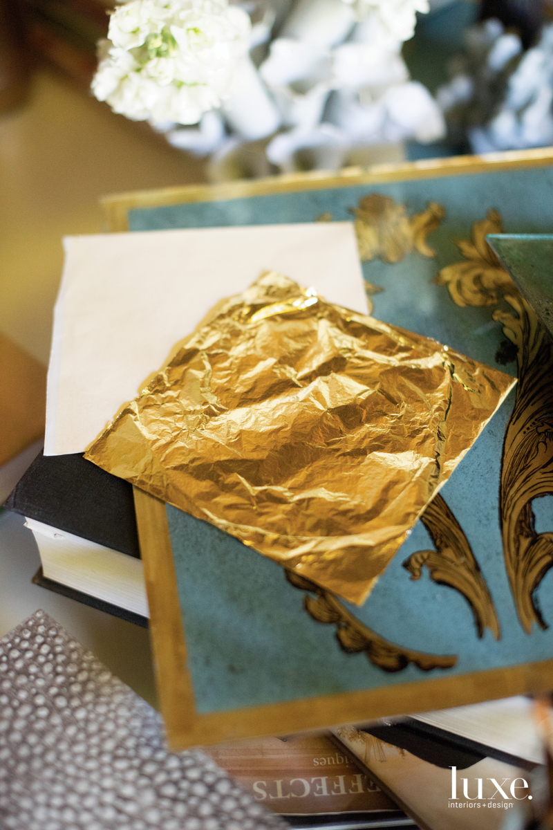 Delicate sheets of gold leaf sit in her creative space.