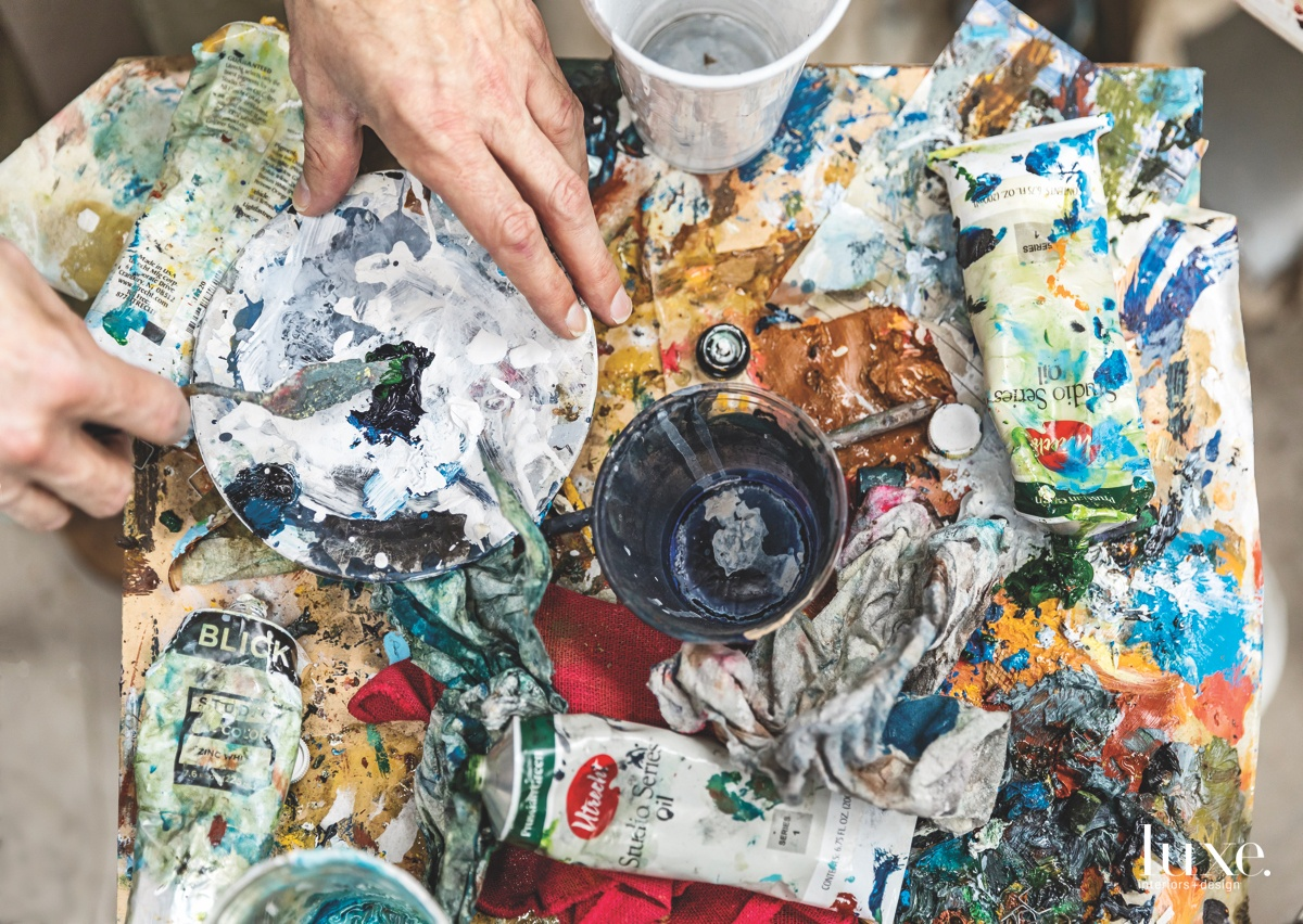 The artist's work space includes a large table-turned-palette--covered in paint tubes, oils, turpenoid, plates and more--where he mixes his paints