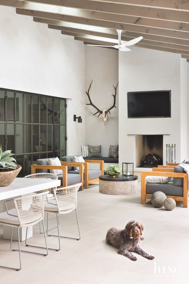 n the back patio of the home, constructed by builder Ben Bailey, chairs by Teak Warehouse with Sunbrella fabric-covered cushions and Kelly Wearstler throw pillows welcome conversation around a stucco fireplace. Texas Lightsmith crafted brass sconces designed by Seiders that frame the door. Metal-base dining chairs, also by Teak Warehouse, surround a cast-concrete dining table