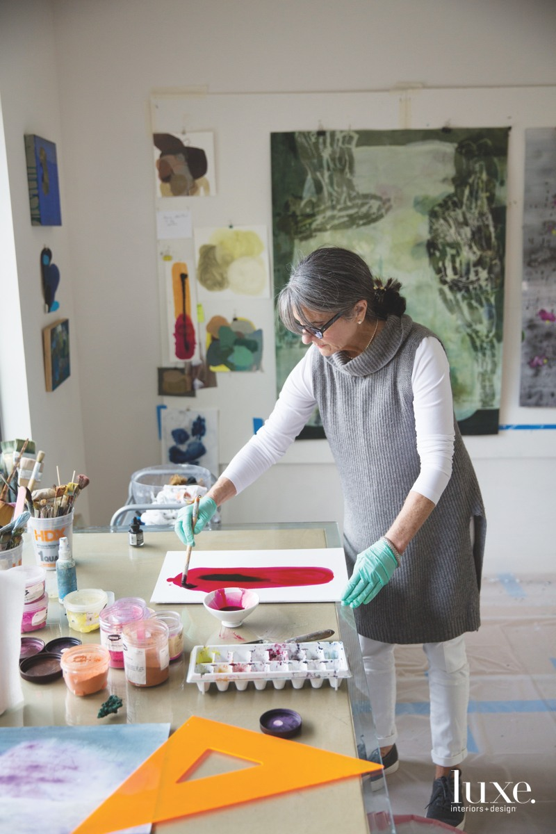 Artist Arienne Lepretre paints daily at a work table in her Dallas studio.