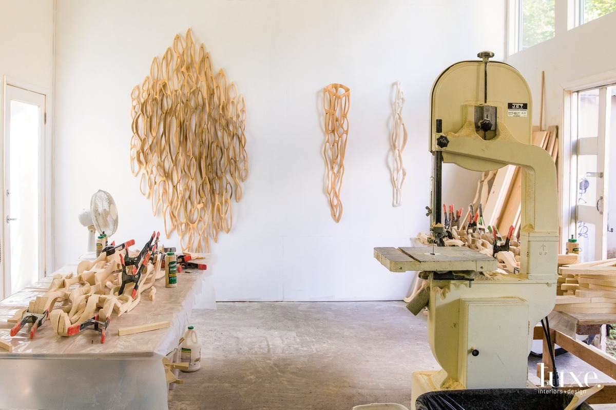 The artist works in a light-filled studio where she assembles her sculptures on a large table and a wall displays completed pieces.