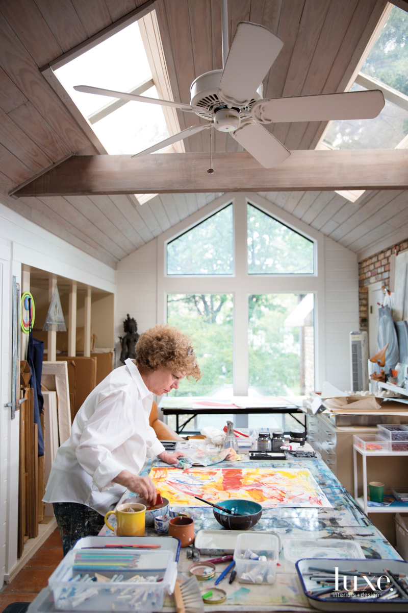 """Russell works at a table she refers to as """"the epicenter"""" of her drawing studio in Dallas."""