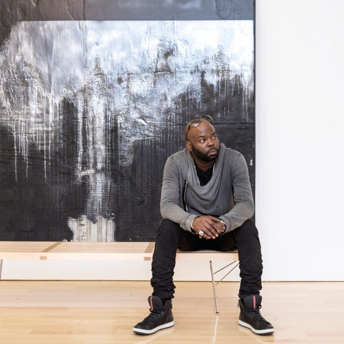 "Dean sits in front of Number 74, a mixed-media piece on view in his exhibition ""Recto/Verso: Duality of a Fragile Ego."""