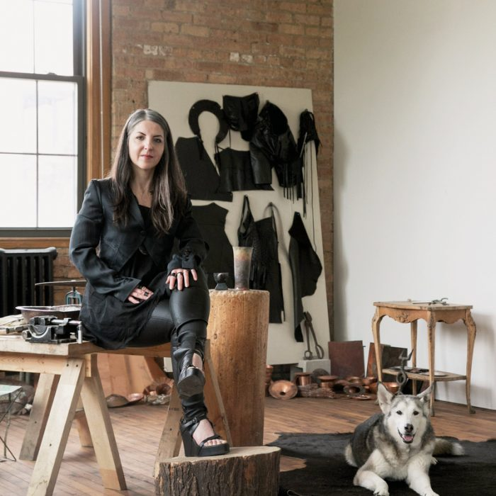 Prieto-Velasco sits with her Siberian Husky, Quinn, in her studio, which is filled with various hammers and bowls.