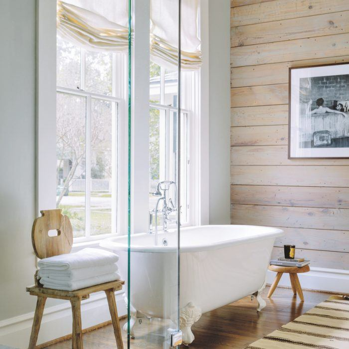 Brandon Fontenot Interiors equipped this Houston bathroom with wall paneling from Historic Houston's Salvage Warehouse --installed by Robert Sanders Homes-- Kohler tub fixtures from Morrison Supply Company, a shade from The Shade Store, a chair from Kuhl-Linscomb and a rug from Carol Piper Rugs.