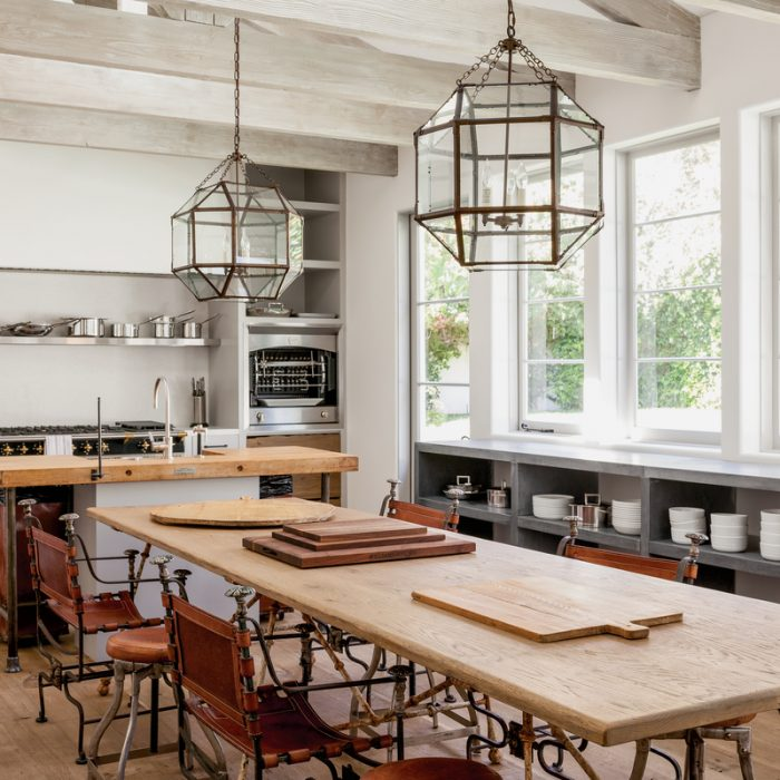 In this Los Angeles, California kitchen designed by Windsor Smith, leather and iron armchairs from Melissa Levinson Antiques sit under Suzanne Kasler pendant lights by Visual Comfort, while a black Lacanche range and rotisserie from La Cornue anchor the far side of the room.