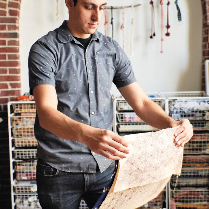 Caleb Sayan holds fabrics at the Textile Hive, the material archive he oversees in Portland.