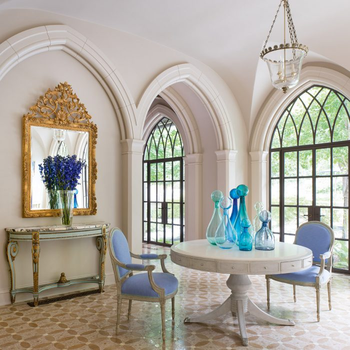 From the new Betty Lou Phillips book, French Refreshed: In this project by Deborah Walker, Louis XVI painted chairs, circa 1890, surround an Iatesta & Co. table. Handblown glass bottles give the garden room a modern twist, while the antique French mirror and console add warmth.