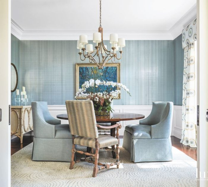 The formal dining room includes a Bausman & Company table, a Niermann Weeks chandelier, and chairs wearing Kravet Couture fabric. Phillip Jeffries' wallcovering from Holly Hunt backs a painting by Bruno Zupan. Draperies are by leejofa.com, the rug is from J. Namnoun Oriental Rug Gallery in Connecticut, and the cabinet is by Michael Taylor Designs. An orchid from Floral Emporium brings the outside in.