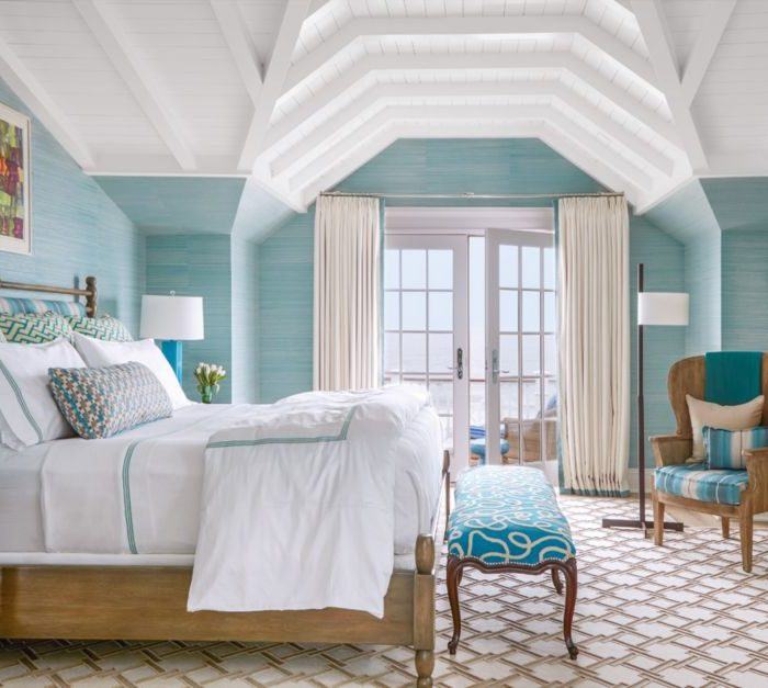 In the master bedroom, nightstands by David Iatesta flank the bed, which is dressed in custom white linens with turquoise and tan details by Cristina Azario. The turquoise stripe on the barrel chair is from Osborne & Little, and the breezy woven draperies are made of Rumba fabric from Romo, trimmed in seafoam slub tape from Lee Jofa.