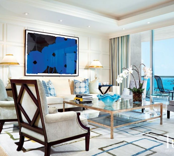 In the living room, two pairs of armchairs—one set pale blue, the other tan and cream—reference sea and sand, while a white sofa allows for Poppies—a bold blue contemporary framed silk screen by Donald Sultan—suspended behind it to make a stunning impact. A wall of windows permits light and the views of the ocean to flood in.