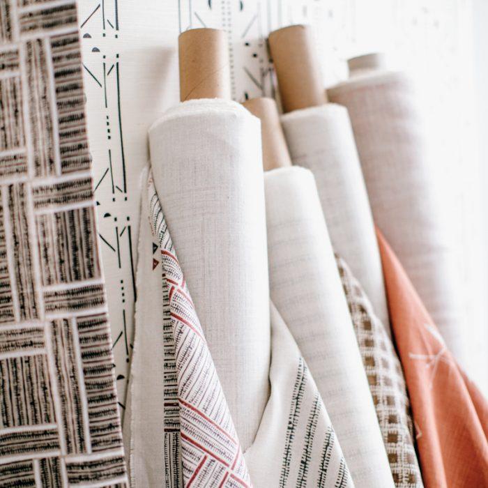 Bolts of Perdigon's fabrics rest on a studio wall.