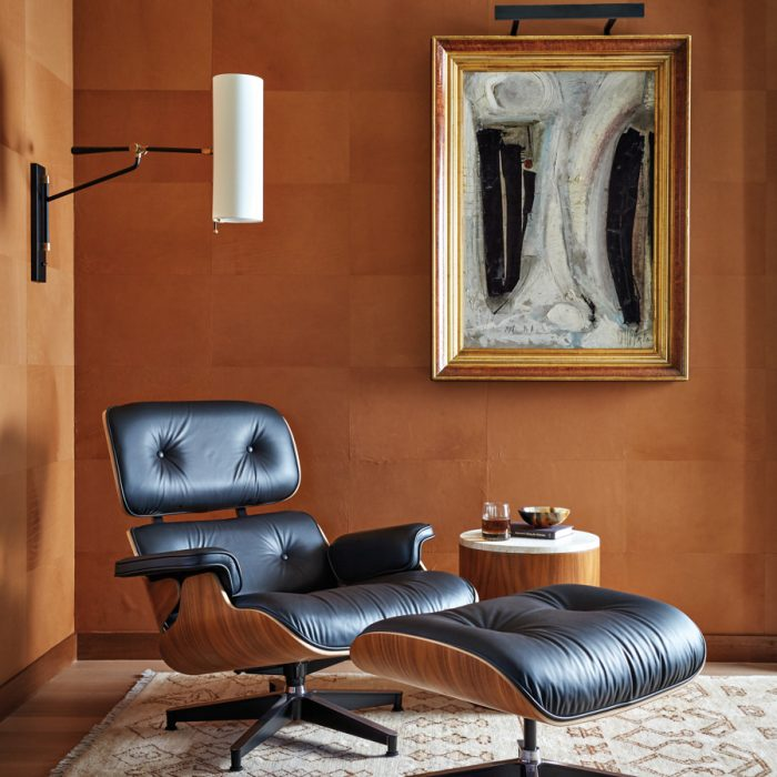 "I conceived the study as a grown-up getaway,"" says Knight. She layered texture with browns and blacks using a leather Ashbury Hides wallcovering, an Eames lounge chair and ottoman, and a Graham Harmon painting. The result is a classic masculine space within which a glass of whiskey is meant to be enjoyed."