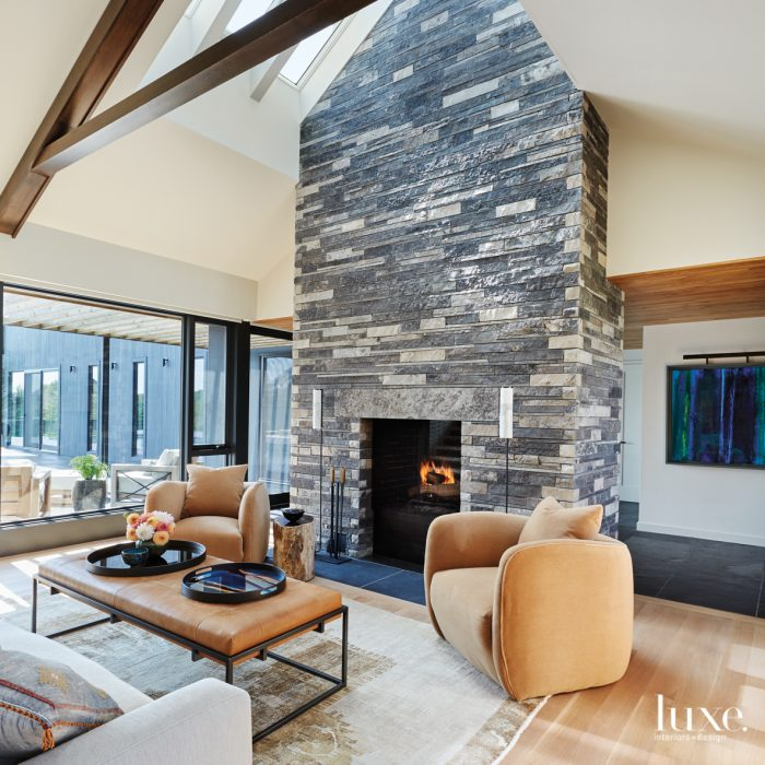 At the centerpiece of the great room is a limestone fireplace designed by architect John Vetter and designer Kimberly Knight. Barrel-backed armchairs by Verellen upholstered in Alpaca velvet by Mokum and a custom cocktail table fabricated by 360 Degrees create a cozy gathering spot.