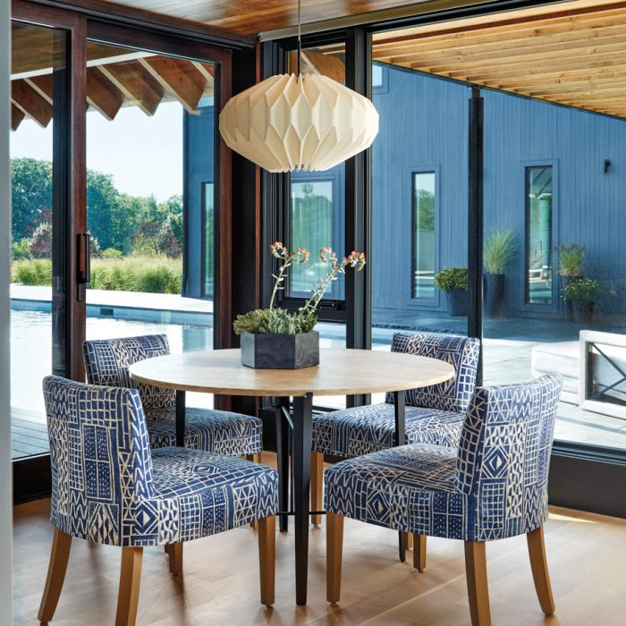 Breakfast is enjoyed with a view. Slipcovered in a lively fabric by William Yeoward from Osborne & Little, a quartet of dining chairs fabricated by Lancaster Custom Crafted Upholstery in Archdale, North Carolina, complements a steel table with a travertine top from Lawson-Fenning in Los Angeles. The handmade folded-linen pendant is by Costa Mesa, California-based artist Michael Towey.