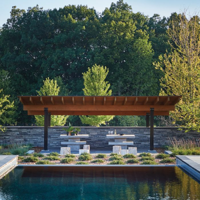 The owners often gather under the pergola at the end of the infinity-edge swimming pool by Neuman Pools, which is enhanced with trees and shrubs selected by Vetter and installed by Nic Ehr Landscape, Co. Inc.