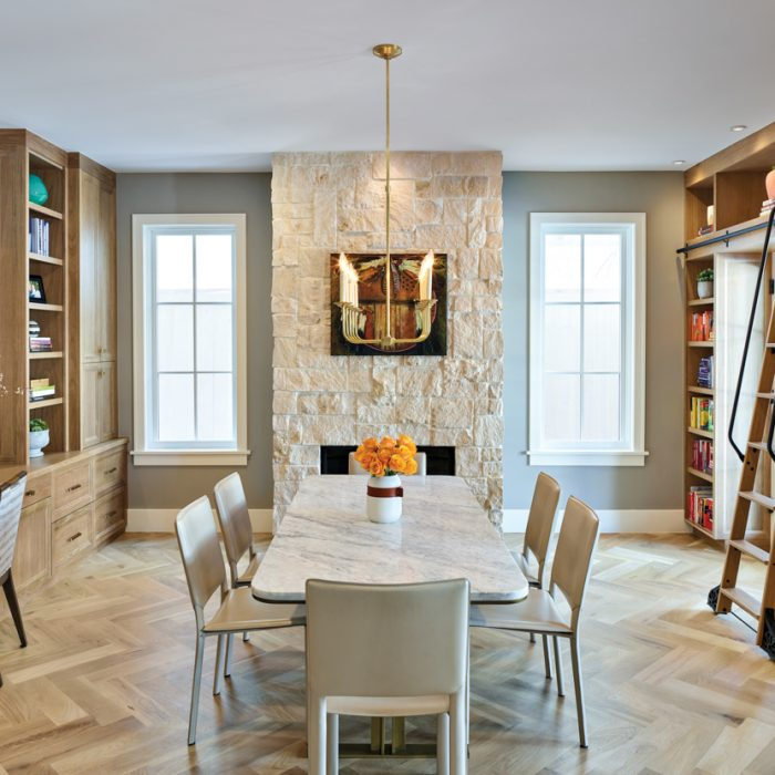 The home office, which doubles as a library, was outfitted with cabinetry and a custom library ladder by Aspen Leaf Kitchens Ltd. The marble-topped conference table with a brass base is from Arhaus. Overhead is a brass chandelier from Fusion Light and Design.